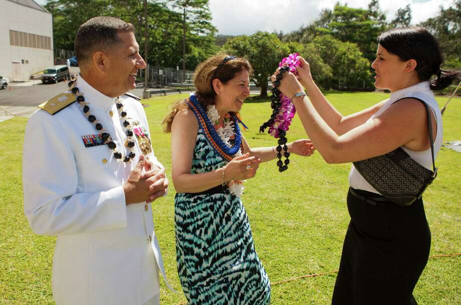 Michelle Donahue (right) places a Hawaiian flower lei on Felicitas Rendon (center) after placing one on new Rear Adm. Jim Rendon. Photo: Marco Garcia, For The Express-News / Marco Garcia