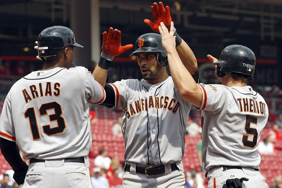 San Francisco Giants' Angel Pagan, center, celebrates with Joaquin Arias (13) and Ryan Theriot (5) after hitting a game-winning, three-run home run off Cincinnati Reds pitcher Sean Marshall during the ninth inning of a baseball game, Thursday, April 26, 2012, in Cincinnati. The Giants won 6-5.