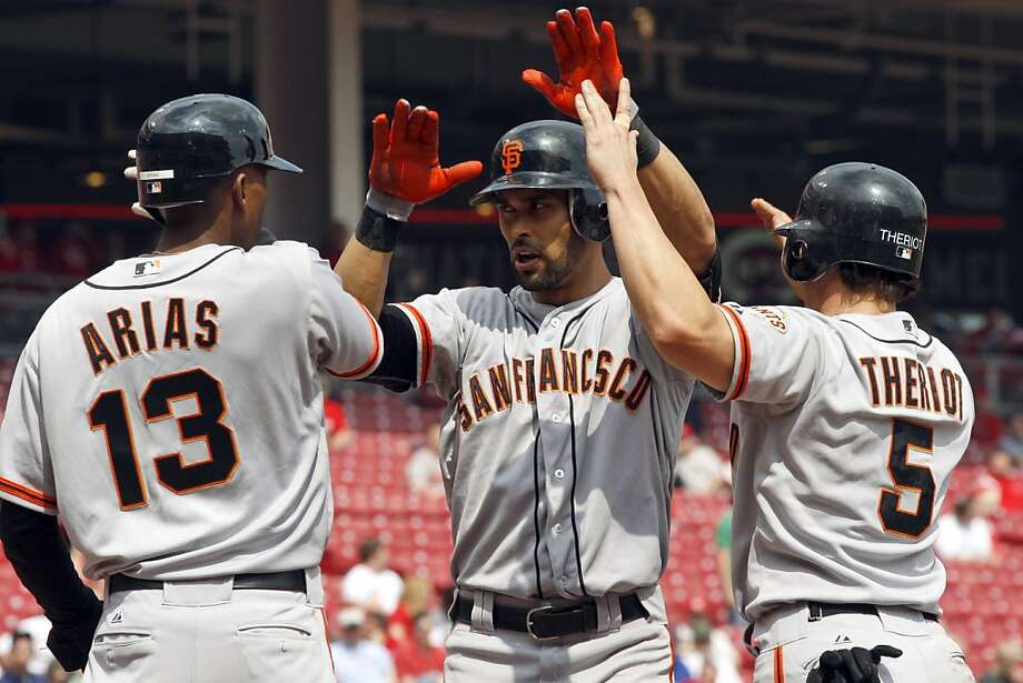 San Francisco Giants' Angel Pagan, center, celebrates with Joaquin Arias (13) and Ryan Theriot (5) after hitting a game-winning, three-run home run off Cincinnati Reds pitcher Sean Marshall during the ninth inning of a baseball game, Thursday, April 26, 2012, in Cincinnati. The Giants won 6-5. Photo: David Kohl, Associated Press