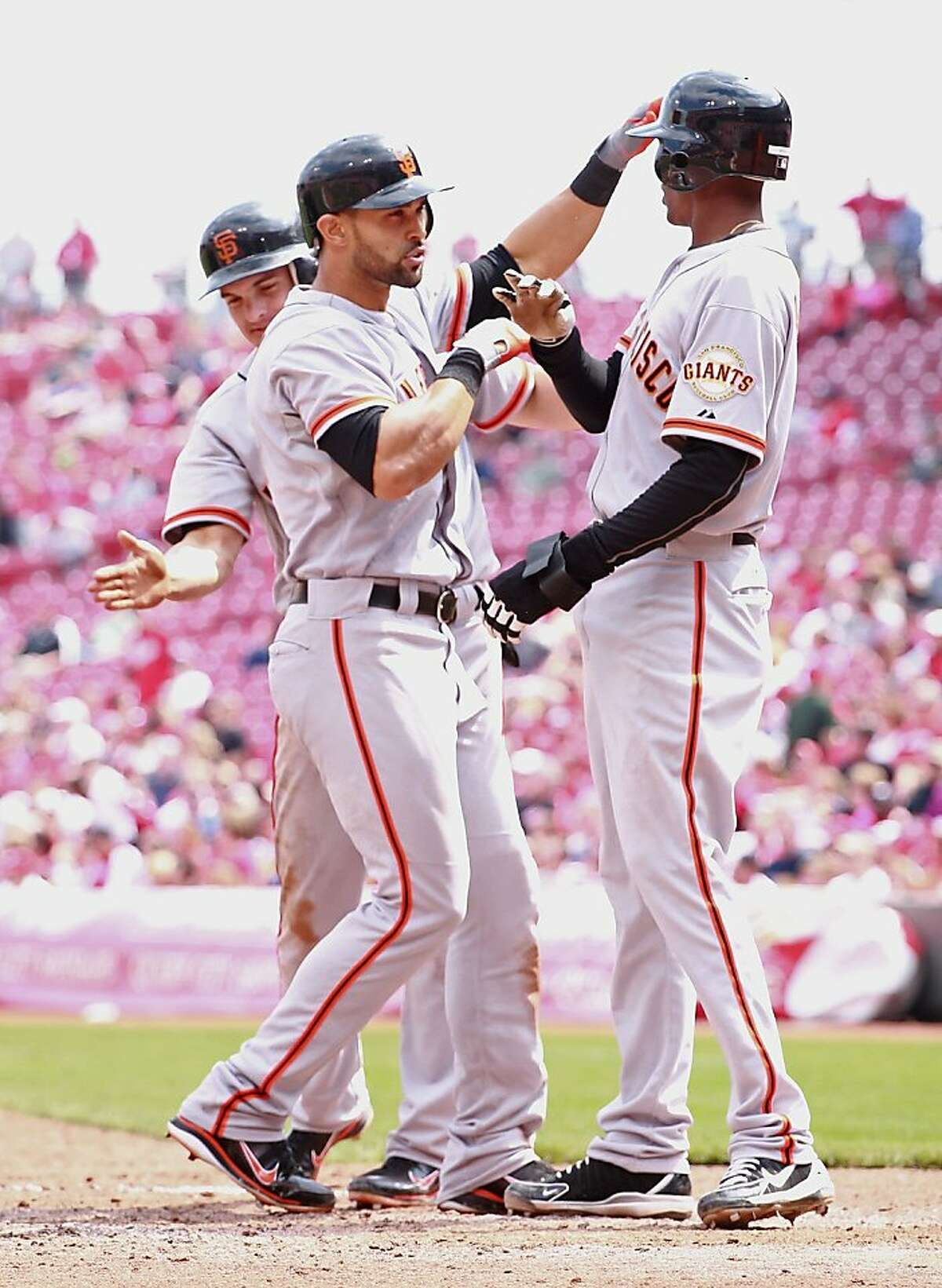 CINCINNATI, OH - APRIL 26: Angel Pagan #16 (center) of the San Francisco Giants is congratulated by Ryan Theriot #5 (left)and Joaquin Arias #13 (right) after Pagan hit a three run home run in the ninth inning of the game against the Cincinnati Reds at Great American Ball Park on April 26, 2012 in Cincinnati, Ohio. The Giants won 6-5. (Photo by Andy Lyons/Getty Images)