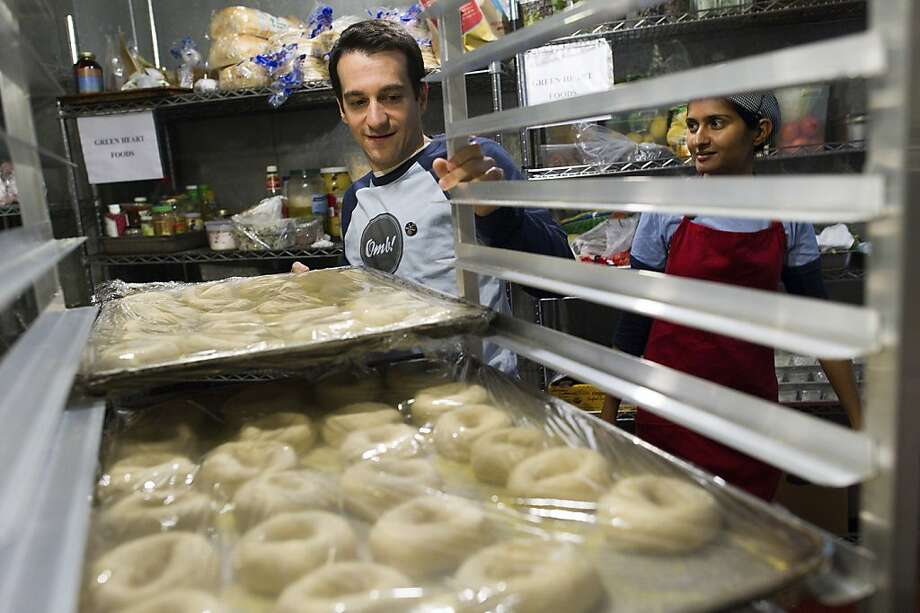 Daniel Scholnick and Deepa Subramanian co-owners of Schmendricks Bagels, stacks up trays of bagels in a kitchen in San Francisco, California, U.S., on Wednesday, April 11, 2012. Photographer: David Paul Morris/Bloomberg *** Local Caption *** Daniel Scholnick;Deepa Subramanian Photo: David Paul Morris, Bloomberg