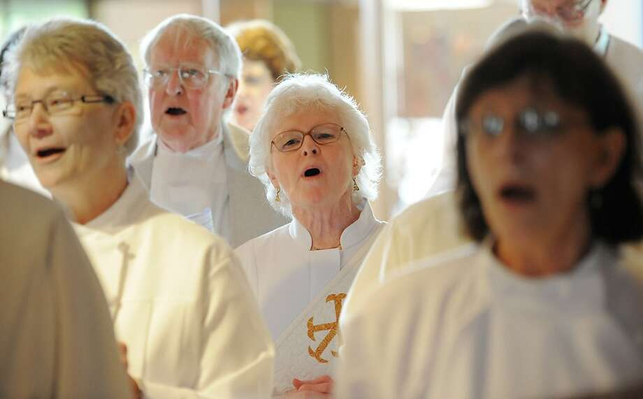 Maria McClain, middle, sings with others before entering the sanctuary of the Freiden's United Church of Christ in Indianapolis, April 15, 2012. The former Catholic nun defied the church's ban on women become priests and went through an ordination ceremony, joining a push to crack open the all-male clergy. (AP Photo/Indianapolis Star, Matt Kryger) Photo: Matt Kryger, Associated Press