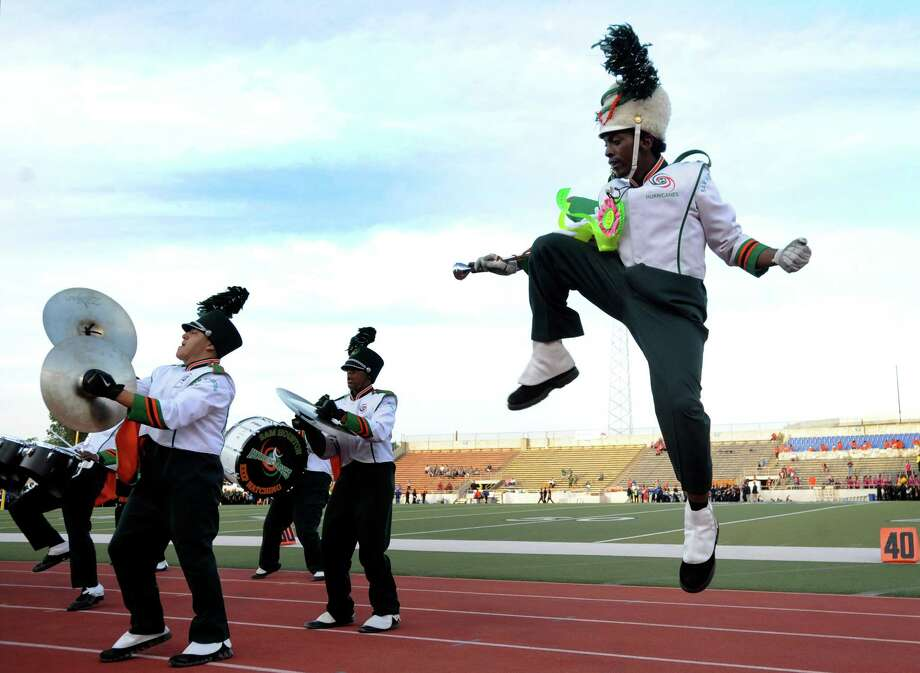 Sam Houston High School drum major Edward Harris leaps as he leads his band during the parade of bands at the 74th Annual Battle of Flowers Band Festival in Alamo Stadium on Thursday, April 26, 2012. Photo: BILLY CALZADA, San Antonio Express-News / SAN ANTONIO EXPRESS-NEWS