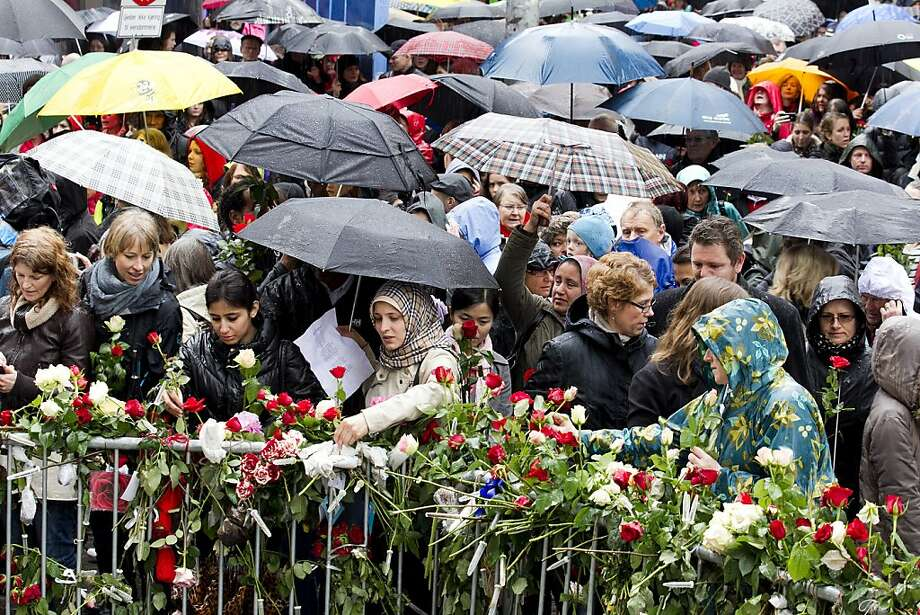 "People gather beside flower decked railings as they participate in a protest during which the gathering sang a song hated by mass murderer Anders Behring Breivik in Oslo on April 26, 2012.   Tens of thousands of rose-waving Norwegians gathered in central Oslo to deride mass murderer Anders Behring Breivik by singing a song he hates, viewing it as Marxist indoctrination. Some 40,000 people, according to police, massed in the rain at a square near the Oslo district courthouse where Breivik is on trial for his July 22 attacks that killed 77 people, to sing ""Children of the Rainbow"" by Norwegian folk singer Lillebjoern Nilsen. Photo: Heiko Junge, AFP/Getty Images"