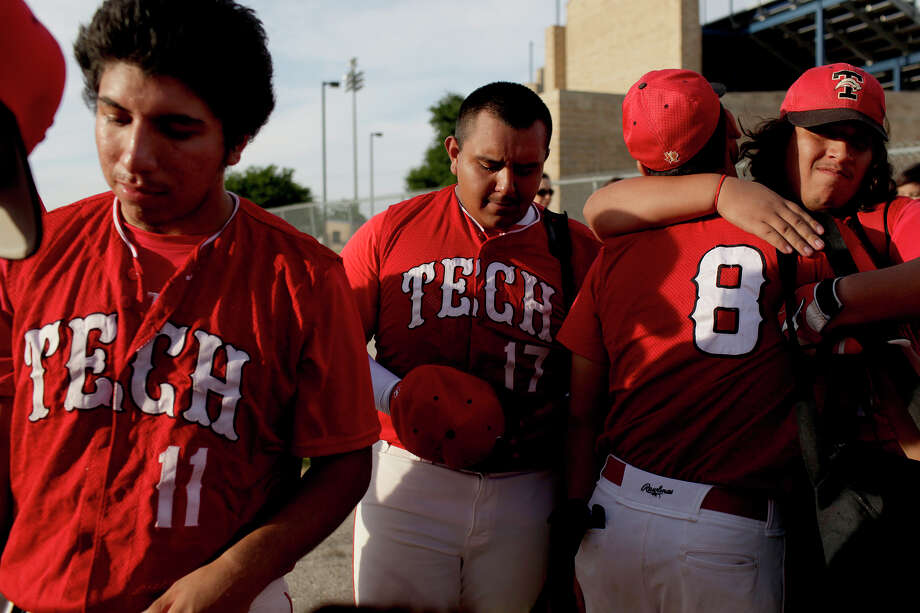 Fox Tech varsity baseball player Joe Martinez is overcome with emotion after their last game while Jacob Rodriguez, far right, embraces Victor Oranday and Daniel Serna, left, waits to sign a baseball for their coach after their last game, against Lanier, at the SAISD Sports Complex in San Antonio on Thursday, April 26, 2012. Fox Tech lost, 10-0. Lisa Krantz/San Antonio Express-News Photo: Lisa Krantz, Express-News / SAN ANTONIO EXPRESS-NEWS