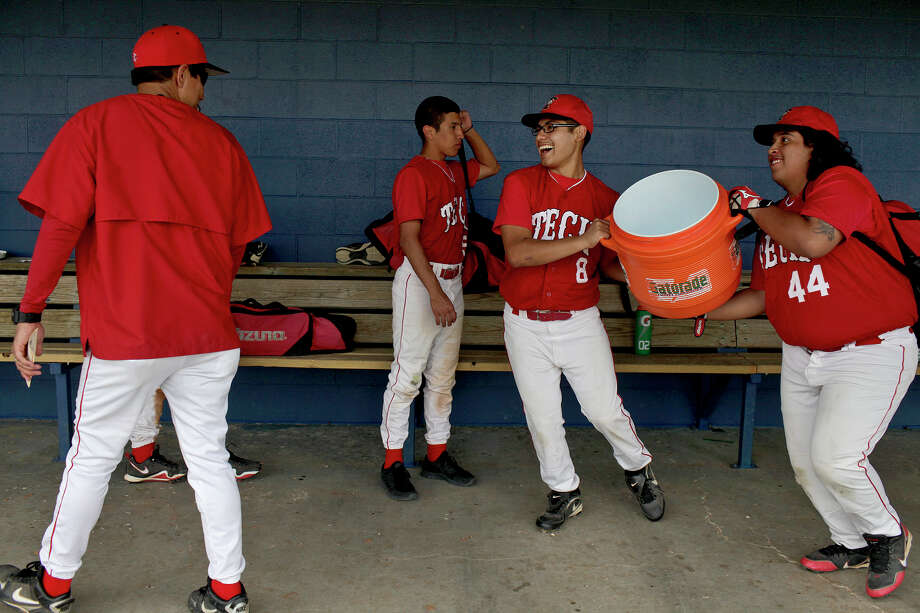 Victor Oranday, right, and Jacob Rodriguez, far right, aim to dump a cooler of ice water on their coach, Adan Velazquez, left, at the conclusion of Fox Tech High School's last game, against Lanier, at the SAISD Sports Complex in San Antonio on Thursday, April 26, 2012. Fox Tech lost, 10-0. At center is Rudy Almendarez. Lisa Krantz/San Antonio Express-News Photo: Lisa Krantz, Express-News / SAN ANTONIO EXPRESS-NEWS