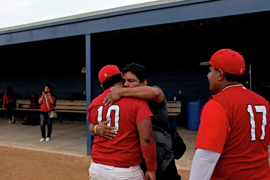 Daniel Manjarrez embraces his son, Fox Tech varsity baseball player Justin Manjarrez, left, as Joe Martinez, right, watches at the conclusion of their last game, against Lanier, at the SAISD Sports Complex in San Antonio on Thursday, April 26, 2012. Fox Tech lost, 10-0. Lisa Krantz/San Antonio Express-News Photo: Lisa Krantz, Express-News / SAN ANTONIO EXPRESS-NEWS
