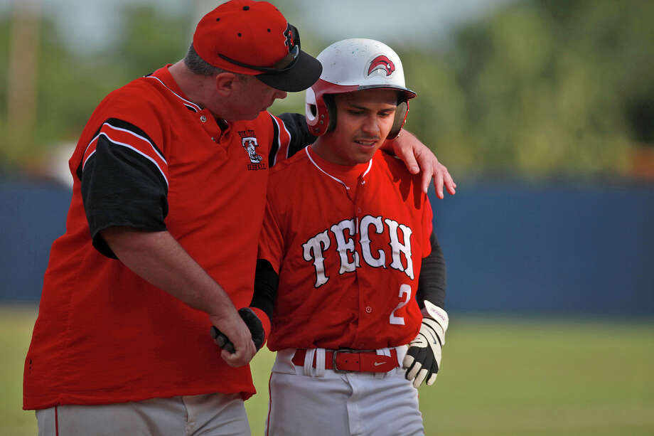 Assistant Coach Eric Otto, left, walks with Cruz Hinojosa after Ramirez made the catch for a third out during Fox Tech High School's last game, against Lanier, at the SAISD Sports Complex in San Antonio on Thursday, April 26, 2012. Fox Tech lost, 10-0. Lisa Krantz/San Antonio Express-News Photo: Lisa Krantz, Express-News / SAN ANTONIO EXPRESS-NEWS