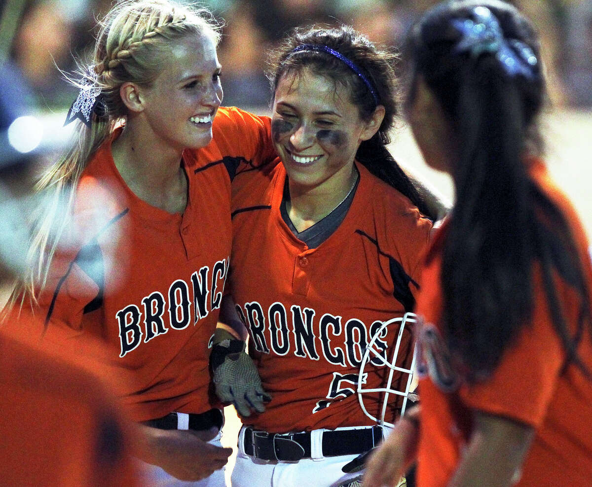 Broncos Christy Trevino (center) is embraced by her pitcher Caleigh Cole after slamming a three run homer to put her team ahead for good as Brandeis beats Southwest 6-4 in playoff action at Southwest High School on April 26, 2012. Tom Reel/ San Antonio EXpress-News