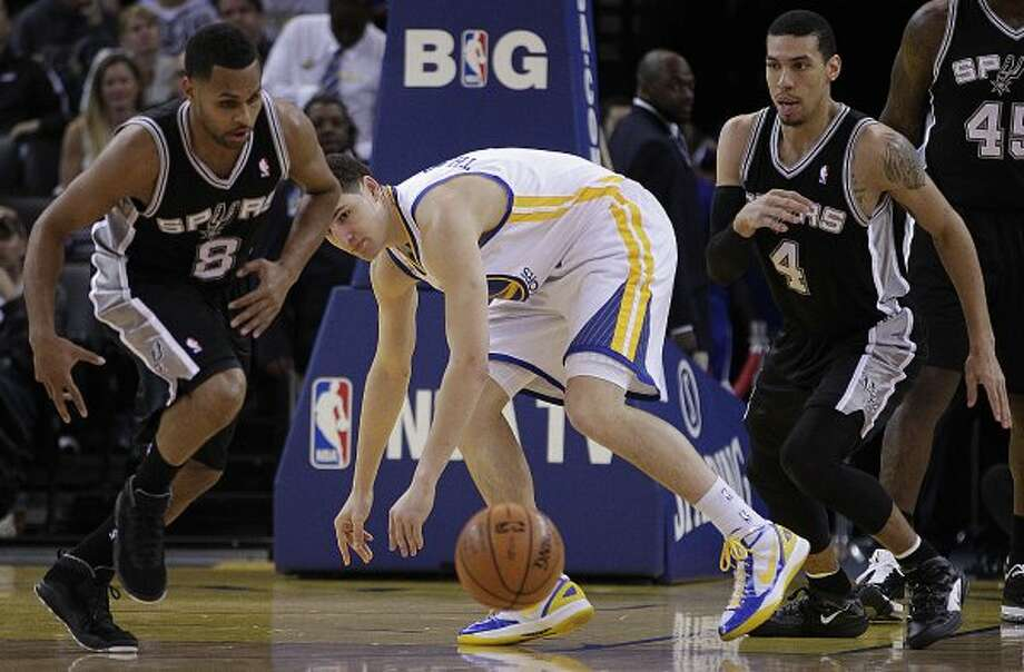 San Antonio Spurs' Patty Mills (8), Golden State Warriors' Klay Thompson, and Spurs' Danny Green (4) eye the loose ball during the first half of an NBA basketball game, Thursday, April 26, 2012, in Oakland, Calif. (AP Photo/Ben Margot) (AP)