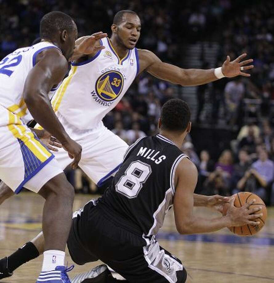 Golden State Warriors' Charles Jenkins, left, and Chris Wright (33) guard San Antonio Spurs' Patty Mills (8) during the first half of an NBA basketball game, Thursday, April 26, 2012, in Oakland, Calif.  The Warriors became the first NBA team in modern history tonight to start five rookies. (AP Photo/Ben Margot) (AP)