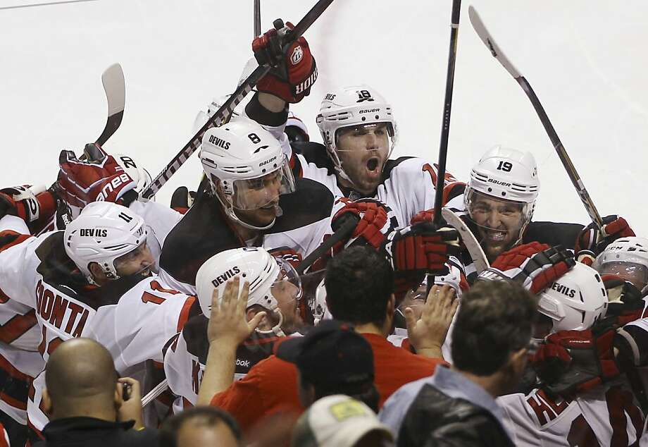 The New Jersey Devils celebrate after defeating the Florida Panthers on a goal by Adam Henrique, lower right, during the second overtime of Game 7 in a first-round NHL Stanley Cup playoff hockey series, in Sunrise, Fla., Wednesday, April 26, 2012. The Devils won 3-2. (AP Photo/J Pat Carter) Photo: J Pat Carter, Associated Press