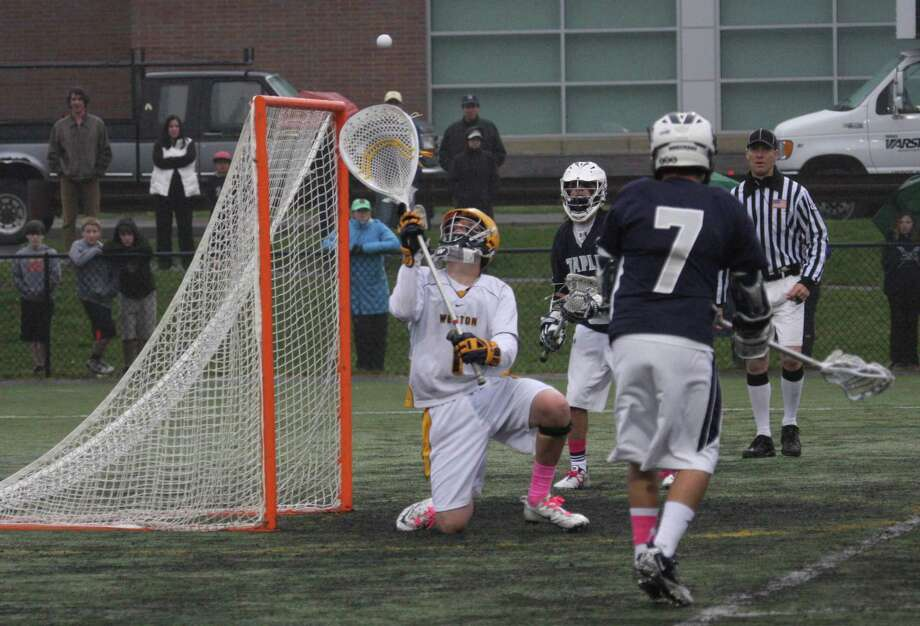 Weston goalie Grant Limone makes the save against Staples Thursday. Limone had 10 saves in Weston's 8-5 victory. Photo: Sharon Furbee / Contributed Phot