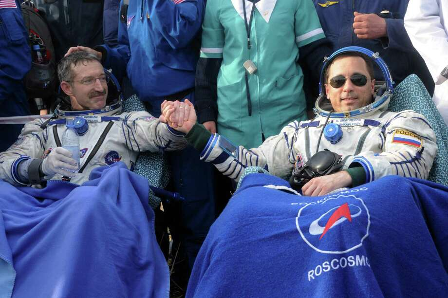 US astronaut Daniel Burbank, left, and Russian cosmonaut Anton Shkaplerov  rest shortly after landing in a Soyuz  capsule outside the town of Arkalyk, Kazakhstan, Friday, April 27, 2012. A Soyuz space capsule carrying Anton Shkaplerov, Anatoly Ivanishin and NASA's Daniel Burbank  touched down safely Friday on the sweeping steppes of central Kazakhstan, ending the men's 163-day stay on the International Space Station. (AP Photo/Kirill Kudryavtsev, Pool) Photo: Kirill Kudryavtsev, Associated Press / Pool AFP
