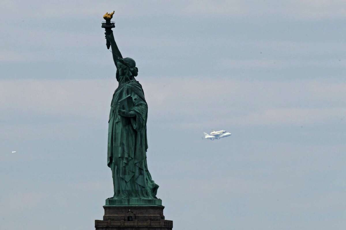 Space shuttle Enterprise, mounted atop a 747 shuttle carrier aircraft, flies past the Statue of Liberty prior to landing at John F. Kennedy International Airport on Friday in New York City. Enterprise, which was flown from Washington, D.C., will eventually be put on permanent display at the Intrepid Sea, Air and Space Museum.