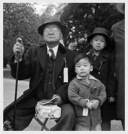 Shigeo Jerry Aso, 3, right, and his brother, Sadao Bill Aso 6, with their grandfather Sakutaro Aso, 70,  were photographed by Dorothea Lange on May 8, 1942 in Hayward, Ca. as they wait for a bus to take them to Tanforan Assembly Center. Sakutaro Aso started the Mt. Eden Laundry in Hayward and sold the business before going to the Tanforan Assembly Center, Topaz and Amache Internment Camps during WWII. Photo: Dorothea Lange, National Archives