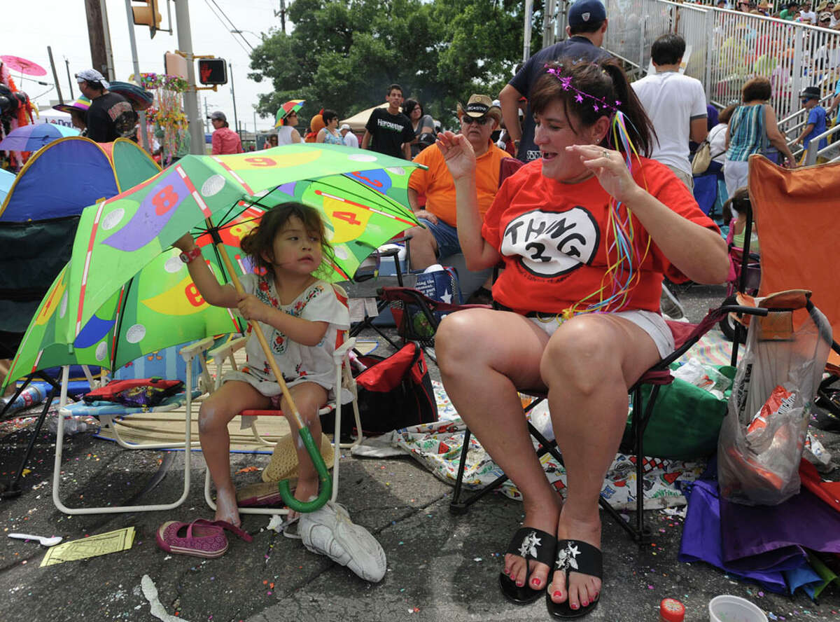 Leah Celeste Espinoza, 3, and her friend, Kathy Torralva, prepare for the start of the Battle of Flowers Parade on April 27, 2012.