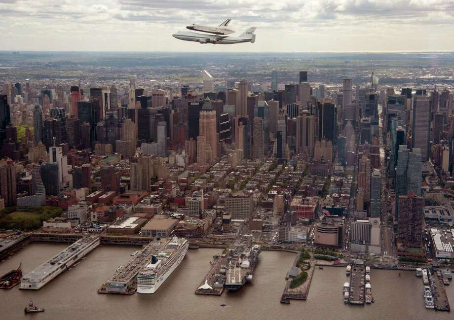 In this photo provided by NASA, Space shuttle Enterprise, riding on the back of the NASA 747 Shuttle Carrier Aircraft, flies over New York on Friday.  Enterprise is eventually going to make its new home in New York City at the Intrepid Sea, Air and Space Museum. Photo: AP
