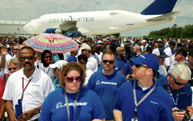 Boeing workers fill up the tarmac as a Boeing Dreamlifter is seen to the rear, the plane that transports the huge fuselage secions, as they wait for the unvieling of the Boeing 787 Dreamliner(not seen) built for Air India to roll out of the hangar during ceremonies April 27, 2012,at Boeing's new production facility in North Charlston, South Carolina.  The ceremony marks Boeing's first South Carolina made 787 Dreamliner aircraft.      AFP PHOTO / Paul J. Richards        (Photo credit should read PAUL J. RICHARDS/AFP/GettyImages) Photo: PAUL J. RICHARDS, AFP/Getty Images / 2012 AFP