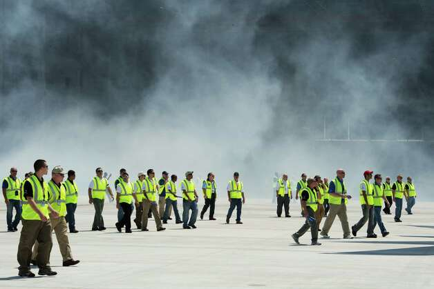 Boeing workers follow a new Boeing 787 Dreamliner(not seen) built for Air India out of the hangar with a smoke machine and fireworks presentation April 27, 2012,at Boeing's new production facility in North Charlston, South Carolina.  The ceremony marks Boeing's first South Carolina made 787 Dreamliner aircraft.     AFP PHOTO / Paul J. Richards        (Photo credit should read PAUL J. RICHARDS/AFP/GettyImages) Photo: PAUL J. RICHARDS, AFP/Getty Images / 2012 AFP