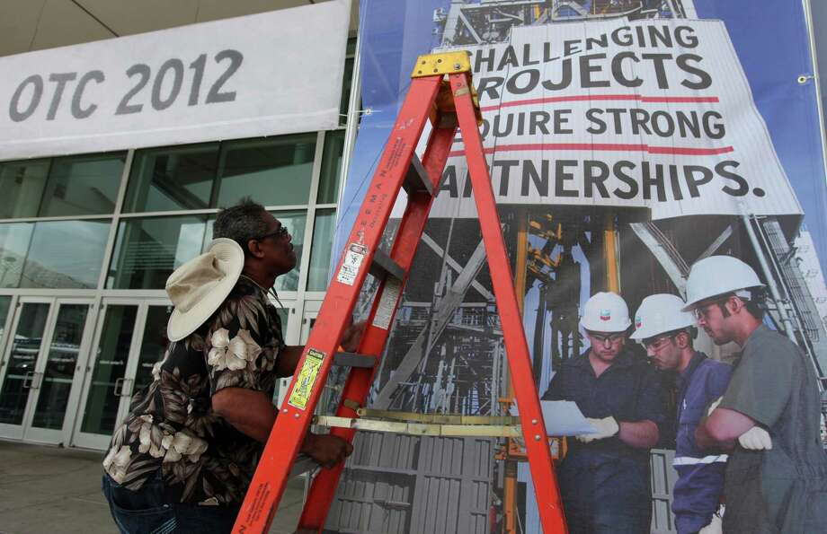 Kenneth Starghill climbs a ladder to secure Offshore Technology Conference signs at Reliant Center on Friday, April 27, 2012, in Houston. Photo: Mayra Beltran, Houston Chronicle / © 2012 Houston Chronicle