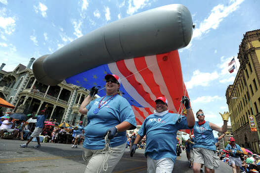 Tetco employees carry an American flag balloon along Broadway during the Battle of Flowers Parade on April 27, 2012. Photo: BILLY CALZADA, Billy Calzada / Express-News / San Antonio Express-News