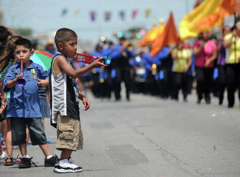 Carlos Rosas, 6, plays a toy trumpet as a marching band passes by during the Battle of Flowers Parade on April 27, 2012. Photo: BILLY CALZADA, Billy Calzada / Express-News / San Antonio Express-News