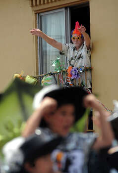 Weldon Albertson, 83, who has been attending the Battle of Flowers Parade and watching from the same room at the Travelodge on Broadway for 44 years, waves at parade participants on April 27, 2012. Photo: BILLY CALZADA, Billy Calzada / Express-News / San Antonio Express-News