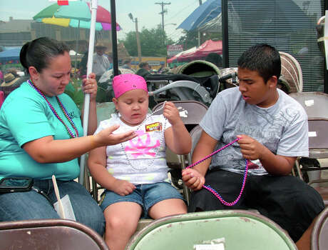 Heaven Sanchez, 8, a second grade student at Powell Elementary is in remission from brain cancer. Heavan's mom, Stephanie Sanchez and brother Anthony Flores, 15, wait for the start of the parade. She and her family were guests at the Battle of Flowers Parade of Tony Martinez of Edmond, Okla., and his cousin Teresa Trevino of San Antonio. Martinez's son Nathaniel died of brain cancer three years ago and was an avid fan of Fiesta. Photo: Pam Howell, Billy Calzada / Express-News / © 2012 San Antonio Express-News