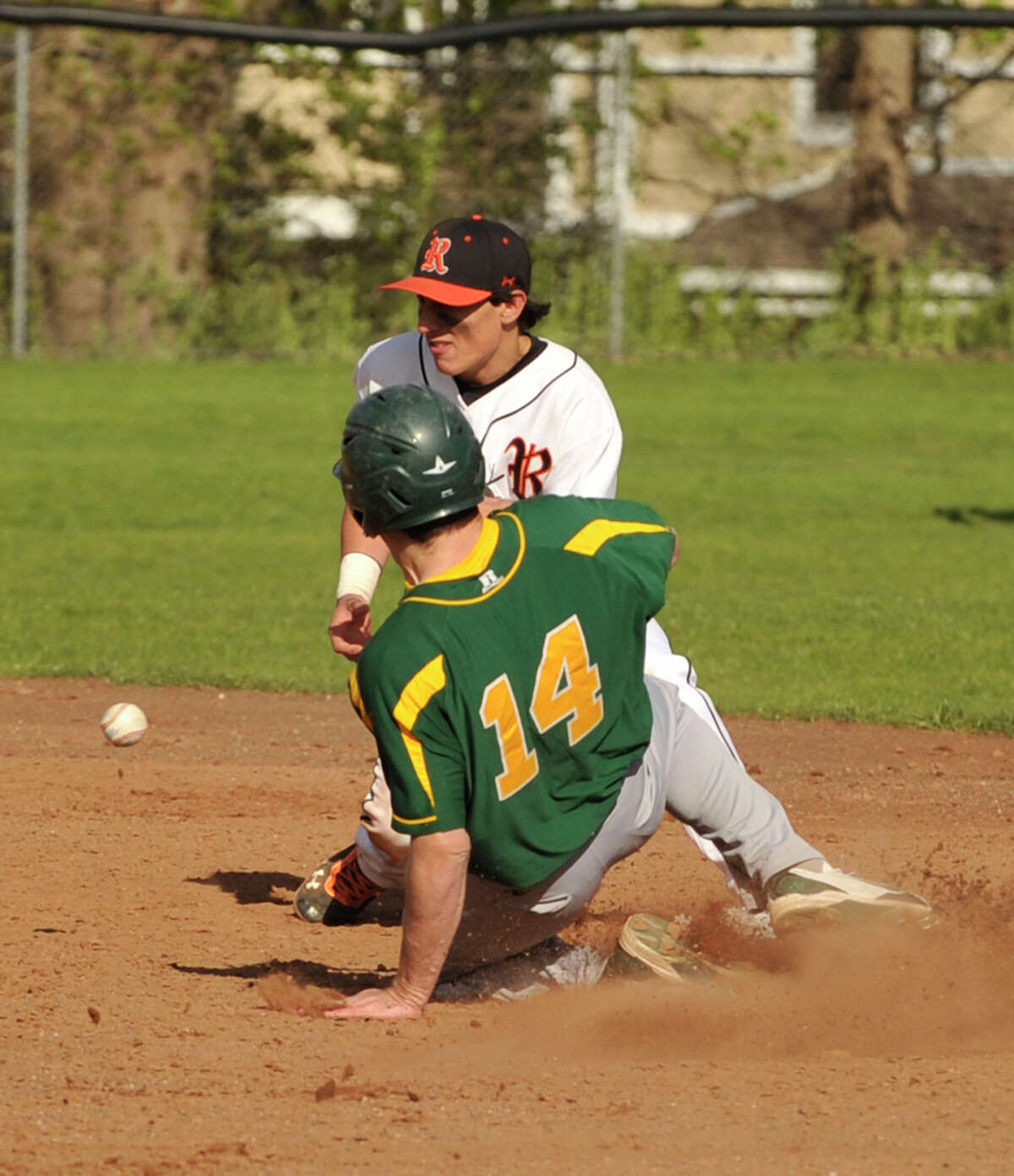 Trinity Catholic's Kevin Epp slides safely into second as Ridgefield's Harrison Siclare fails to come up with the ball during their game at the Old High School Field in Ridgefield, Conn., on Friday, April 27, 2012.
