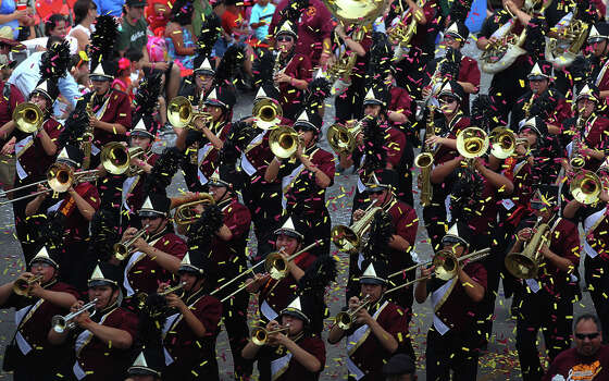 The Harlandale High School marching band plays for parade spectators in a sea of confetti at the 2012 Battle of Flowers parade on Apr. 27, 2012. Photo: KIN MAN HUI,  Kin Man Hui/Express-News / ©2012 San Antonio Express-News