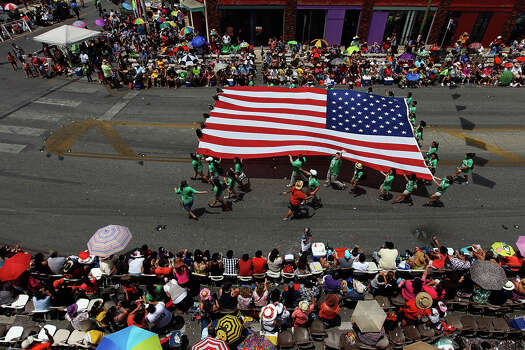 The U.S. Flag is carried along the route near Broadway and Jones at the 2012 Battle of Flowers parade on Apr. 27, 2012. Photo: KIN MAN HUI,  Kin Man Hui/Express-News / ©2012 San Antonio Express-News