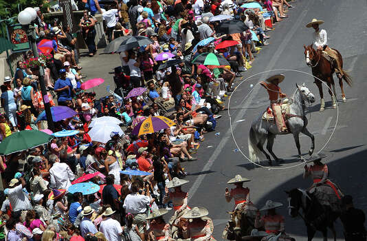 A vaquero twirls his lasso for parade spectators while heading down Commerce Street at the 2012 Battle of Flowers parade on Apr. 27, 2012.. Photo: KIN MAN HUI,  Kin Man Hui/Express-News / ©2012 San Antonio Express-News