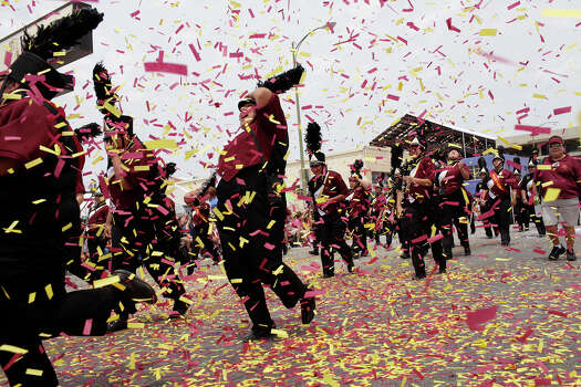 Confetti blown by the family of Harlandale High School cymbal player Jake Ryan Villarreal is blown as the Harlandale band passes their seats during the Battle of Flowers Parade on Friday, April 27, 2012. Photo: Lisa Krantz, SAN ANTONIO EXPRESS-NEWS / SAN ANTONIO EXPRESS-NEWS