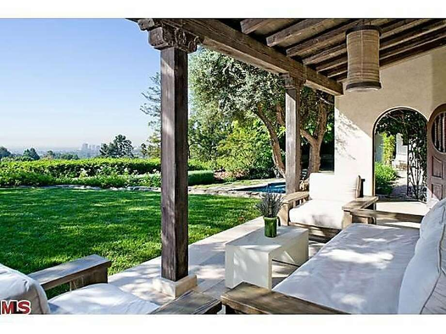 The property features a covered patio area with a view of the beautifully landscaped grounds. Photo: Courtesy Of Realtor.com