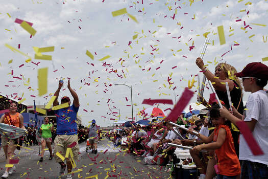 The family of Harlandale High School cymbal player Jake Ryan Villarreal, right, blows confetti as the band passes their seats during the Battle of Flowers Parade on Friday, April 27, 2012.  Photo: Lisa Krantz, SAN ANTONIO EXPRESS-NEWS / SAN ANTONIO EXPRESS-NEWS