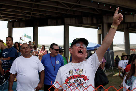 """Richard Salas, the self-appointed president of the """"Parade Squatters Association,"""" cheers from his family's spot on Broadway during the Battle of Flowers Parade on Friday, April 27, 2012. Photo: Lisa Krantz, SAN ANTONIO EXPRESS-NEWS / SAN ANTONIO EXPRESS-NEWS"""
