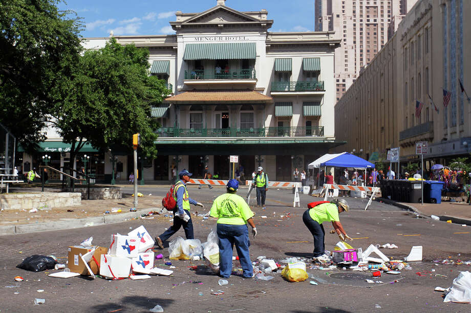 Workers collect trash along Alamo St after the Fiesta Battle of Flowers Parade, Friday, April 27, 2012. Photo: JENNIFER WHITNEY, Jennifer Whitney/ Special To The Express-News / special to the Express-News
