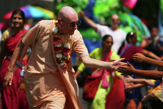A member of the Hare Krishna Temple slaps hands as he walks along Commerce St during the Fiesta Battle of Flowers Parade, Friday, April 27, 2012. (JENNIFER WHITNEY) Photo: JENNIFER WHITNEY, Jennifer Whitney/ Special To The Express-News / special to the Express-News