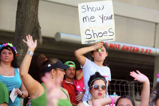 """A girl holds a """"show me your shoes"""" sign along Commerce St. during the Fiesta Battle of Flowers Parade, Friday, April 27, 2012. (JENNIFER WHITNEY) Photo: JENNIFER WHITNEY, Jennifer Whitney/ Special To The Express-News / special to the Express-News"""