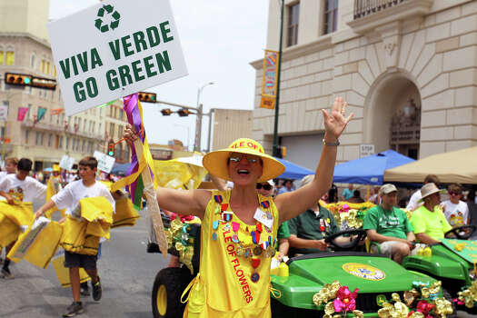 """A member of the Battle of Flowers Association holds a """"Go Green"""" sign at the beginning of the Fiesta Battle of Flowers Parade, Friday, April 27, 2012. (JENNIFER WHITNEY) Photo: JENNIFER WHITNEY, Jennifer Whitney/ Special To The Express-News / special to the Express-News"""