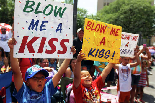 """From left, Ernest Hernandez, 8, Ryan Chavez, 5, and Jeremy Chavez, 7, hold """"Blow Me A Kiss"""" signs as queens pass along Commerce St during the Fiesta Battle of Flowers Parade, Friday, April 27, 2012. (JENNIFER WHITNEY) Photo: JENNIFER WHITNEY, Jennifer Whitney/ Special To The Express-News / special to the Express-News"""