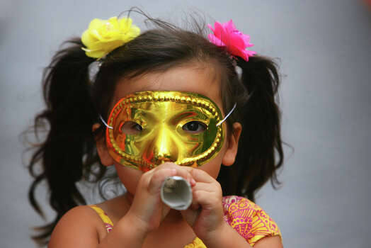 Kassandra Falcon, 3, blows a horn as the parade passes along Commerce St. during the Fiesta Battle of Flowers Parade, Friday, April 27, 2012. (JENNIFER WHITNEY) Photo: JENNIFER WHITNEY, Jennifer Whitney/ Special To The Express-News / special to the Express-News