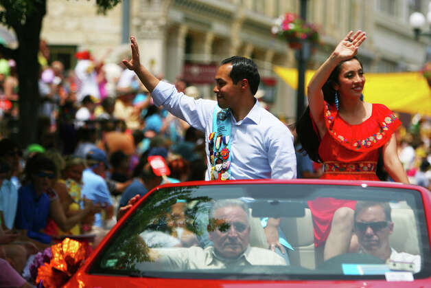 Mayor Julian Castro and his wife, Erica, wave as their car passes in front of the Alamo during the Fiesta Battle of Flowers Parade, Friday, April 27, 2012. (JENNIFER WHITNEY) Photo: JENNIFER WHITNEY, Jennifer Whitney/ Special To The Express-News / special to the Express-News