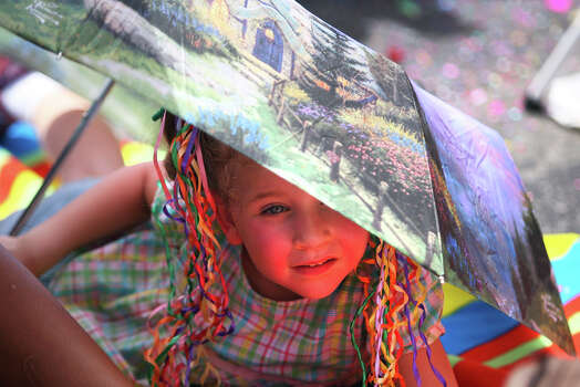 Audri Woodard, 4, watches the parade from under an umbrella during the Fiesta Battle of Flowers Parade, Friday, April 27, 2012. (JENNIFER WHITNEY) Photo: JENNIFER WHITNEY, Jennifer Whitney/ Special To The Express-News / special to the Express-News