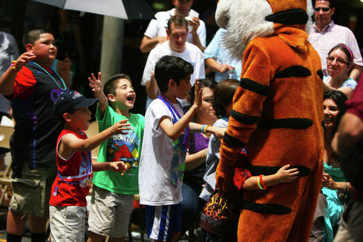 A group of kids waits to hug the Trinity University Tiger along Commerce St. during the Fiesta Battle of Flowers Parade, Friday, April 27, 2012. (JENNIFER WHITNEY) Photo: JENNIFER WHITNEY, Jennifer Whitney/ Special To The Express-News / special to the Express-News