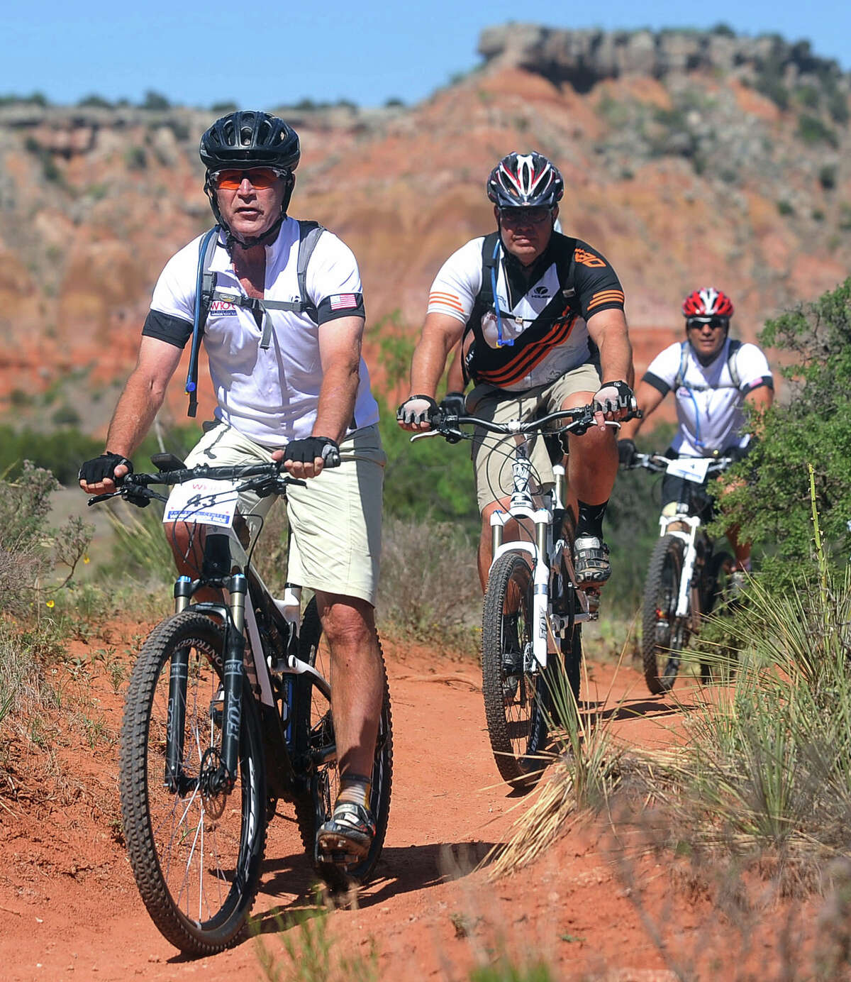 President George W. Bush leads a pack of riders on a trail during the second day of The Bush Center Warrior 100k, Friday, April 27, 2012 at Palo Duro Canyon State Park in Canyon, Texas.