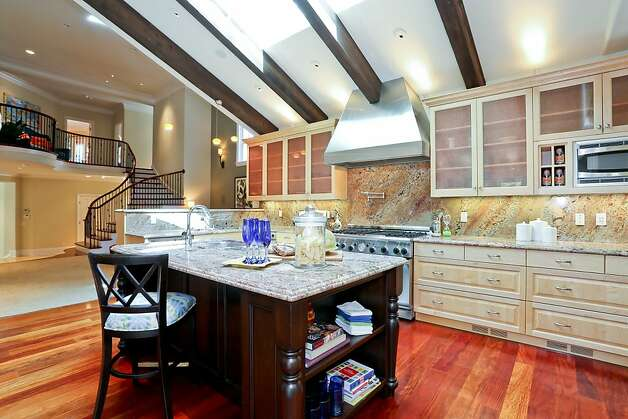 Glass-front cabinetry, hardwood floors and granite countertops are among the many elegant features of the kitchen, which also has an exposed wood-beam ceiling. Photo: Michael Bonocore, VHT Visual Marketing Services