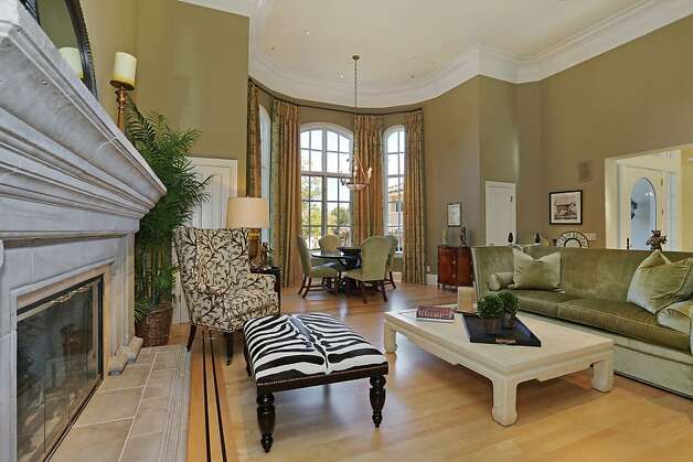 The formal living room features hardwood floors under tall crown molding along with a wide fireplace and bay window. Photo: Michael Bonocore, VHT Visual Marketing Services