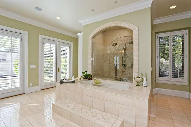 The elegance of the bathroom in the master suite includes a large jetted tub, his-and-her vanities and French doors leading to a private outdoor spa area. Photo: Michael Bonocore, VHT Visual Marketing Services